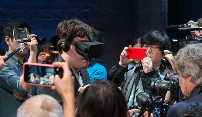 wearing the oculus rift surrounded by journalists
