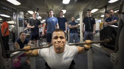 How to beat gym anxiety - men crowding a man struggling to lift weights