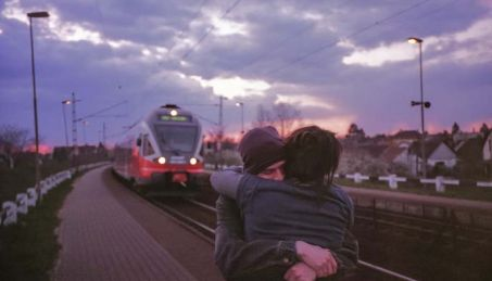 long distance couple hugging goodbye at trainstation