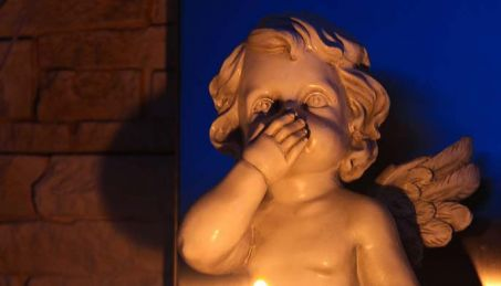 cherub with hand over mouth