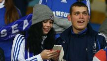 Boyfriend and girlfriend in football t-shirts watching a game