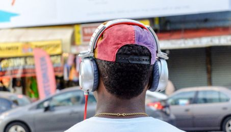 guy listening to exlusive albums on music streaming sites with headphones