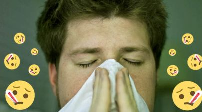 boy sick at uni sneezing into tissue